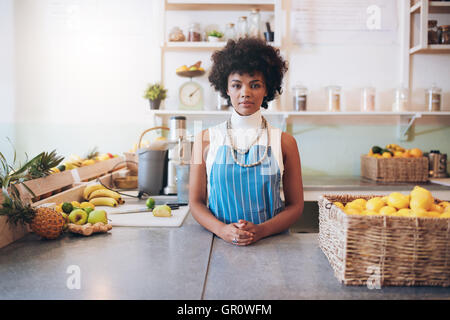 Portrait of young african woman wearing apron standing behind juice bar counter looking at camera. - Stock Photo
