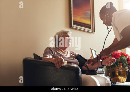 Home healthcare nurse checking blood pressure of senior woman. Elderly woman sitting on chair at home with female - Stock Photo