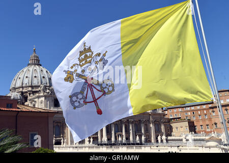 A flag with the coat of arms of Vatican City waves in Vatican City, 02 September 2016. St. Peter's Basilica can - Stock Photo