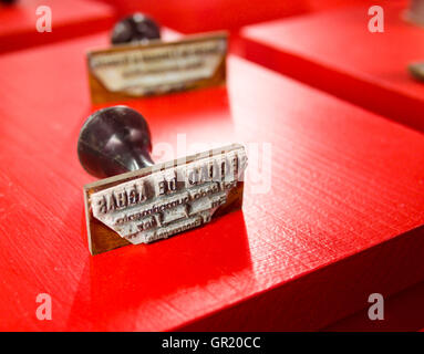 Rubber Stamps on Red. A pair of rubber stamps displayed on a bright red board. Seggao de Aghas. Thinking Section. - Stock Photo