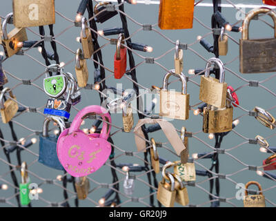 Love Locks on the bridge in pink. Padlocks decorate a bridge over the Salz river.  LED bulbs also provide decoration. - Stock Photo