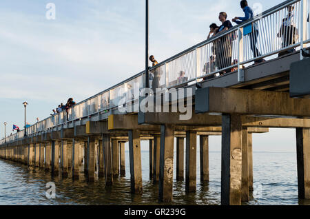 People looking out to sea on the Steeplechase wooden pier on Coney Island beach and boardwalk, New York - Stock Photo