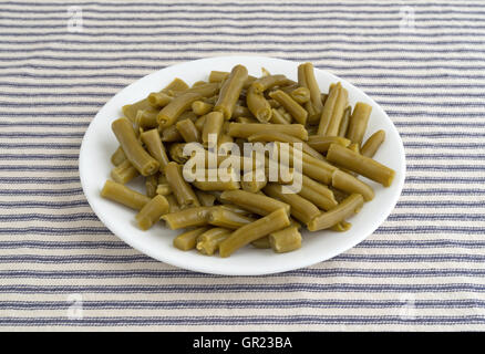 A serving of organic cut green beans on a striped tablecloth. - Stock Photo