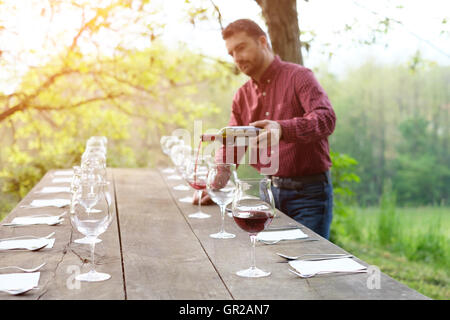 portrait of wine producer pouring red wine into wine glasses Stock Photo