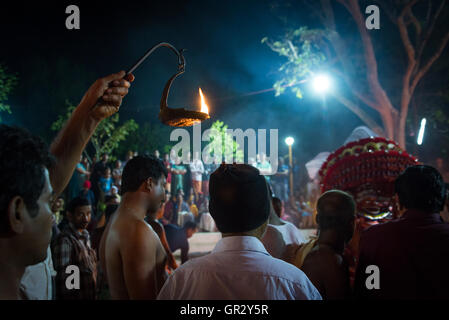 A man holds a flame aloft to illuminate the proceedings at a theyyam ritual in a northern Keralan village near Kannur - Stock Photo