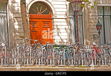 Typical scene along canal in Amsterdam, Holland, with parked bikes in front of houses - Stock Photo