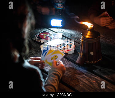 Kids play the card game Uno by an oil candle while Camping in French Creek State Park Pennsylvania