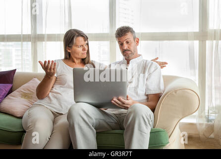 middle aged couple looking at a computer and having a disagreement - Stock Photo