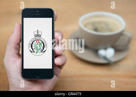 A man looks at his iPhone which displays the UK Government Supreme Court crest (Editorial use only). - Stock Photo