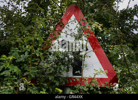 An obscured warning sign from the Highway Code, junction on bend ahead. - Stock Photo