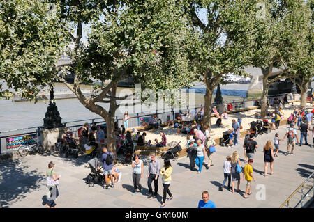 London's South Bank in summer.  People strolling along the Thames Path next to the temporary beaches set up by the - Stock Photo