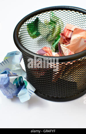 Wasting money concept. Throwing money away. Money in wastepaper basket. Losing money. wasteful spending. wasteful - Stock Photo