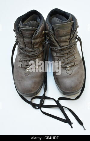 Dirty old boots isolated on white background hiking style. Bon voyage. Hiking style used boots, it was a great trip. - Stock Photo