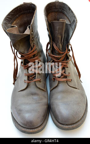 Dirty old boots isolated on white background military style. Dirty old boots in need of cleaning. Boots on the ground. - Stock Photo