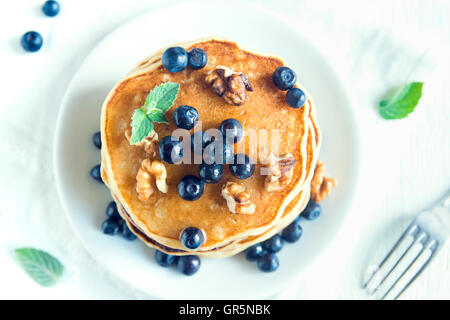 Homemade pancakes with blueberry, honey and walnuts for breakfast (top view) - Stock Photo
