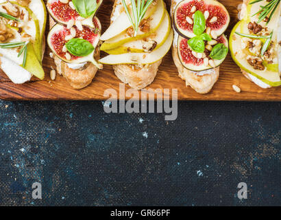 Crostini with pear, ricotta cheese, figs, nuts and fresh herbs - Stock Photo