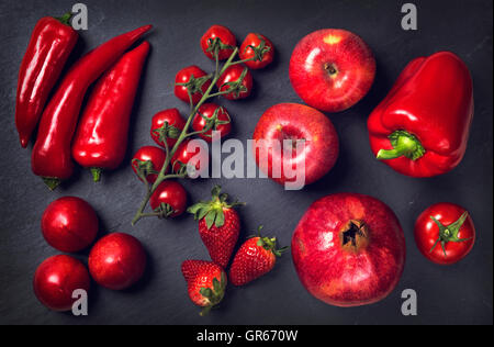 Red healphy vegetables and fruits on a black slates - Stock Photo