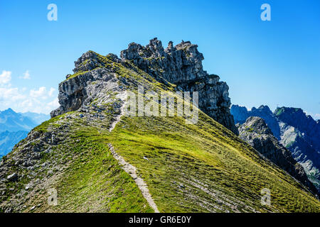 Path leading up to top of little mountain facing the Alps under blue sky in Allgau Germany - Stock Photo