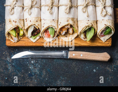 Tortilla wraps with different fillings on dark grey concrete background - Stock Photo