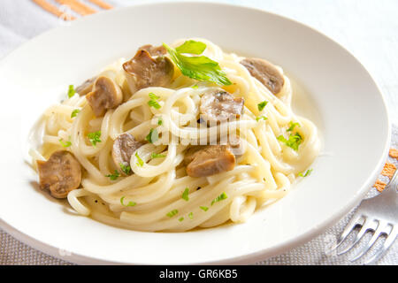 Spaghetti pasta with grilled mushrooms and greens on white plate close up - Stock Photo