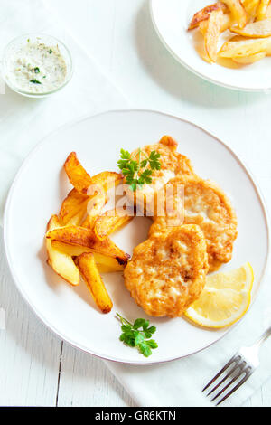 Homemade fish cakes with french fries on white plate close up - Stock Photo