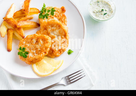Homemade fish cakes with french fries on white wooden background with copy space - Stock Photo