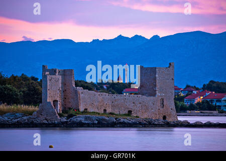Island of Vir dawn view, fortress and Velebit mountain, Dalmatia, Croatia - Stock Photo