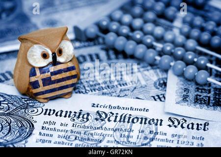 Greek Owl Sitting On Old German Inflation Money, German Reparations - Stock Photo