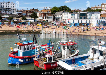 Broadstairs resort town, view from harbour of fishing boats and then main beach packed with people on hot summer - Stock Photo