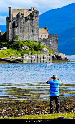 Man Taking Photos Of Eilean Donan Castle, Dornie, Western Ross-Shire, Scottland, Uk - Stock Photo