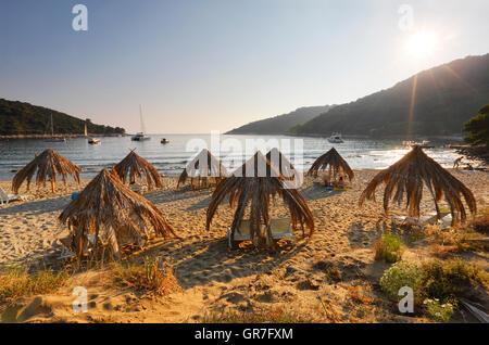 Straw umbrellas in Saplunara sand beach on island Mljet - Stock Photo