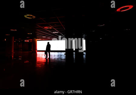Man Running Alone Through An Underground Hall Towards The Emergency Exit - Stock Photo