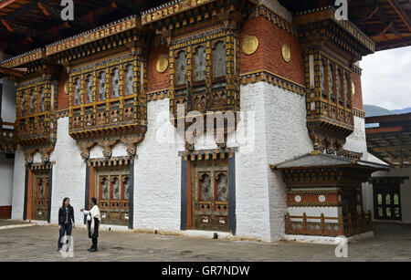 Local Guide With Visitor In The Courtyard Of The Monastery And Fortress Punakha Dzong, Punakah, Bhutan - Stock Photo