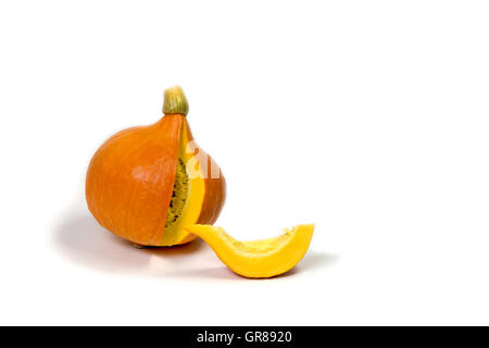 Sliced pumpkin is lying on a white background. A piece of pumpkin is lying in front. - Stock Photo