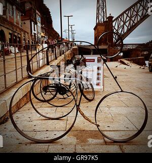 Bicycles Parked On Sidewalk Against Sky - Stock Photo