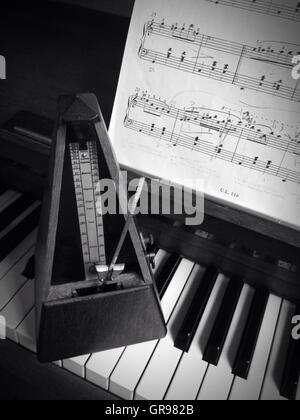 Close-Up Of Metronome On Piano By Musical Note At Home - Stock Photo