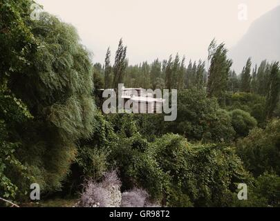 Shigar Fort Residence Amidst Green Trees Against Sky - Stock Photo