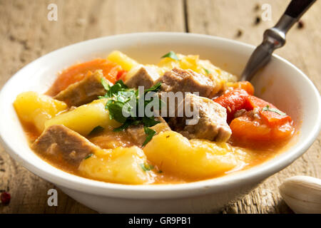 Homemade stew with meat and vegetables in bowl with ingredients over rustic wooden table - Stock Photo