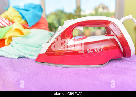 Iron and pile of clothes for ironing. - Stock Photo
