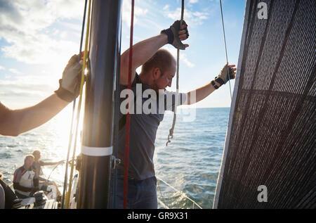 Man adjusting sailing rigging on sailboat - Stock Photo