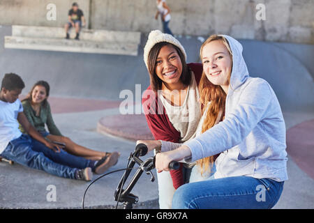 Portrait smiling teenage girls with BMX bicycle at skate park - Stock Photo