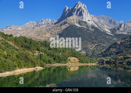 Foratata peak reflected in the Lanuza reservoir in the Tena Valley, Pyrenees of Huesca, Spain. - Stock Photo