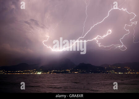 Lightning over the mountains and lake - Stock Photo