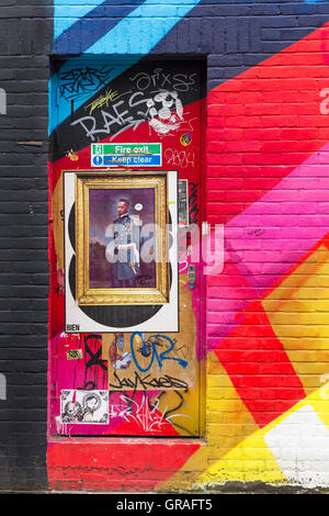 Graffiti on door with framed picture and colourful mural graffiti on wall at Shoreditch, London in September - Stock Photo