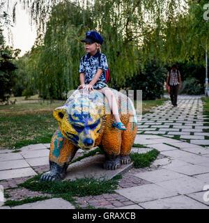 Boy Sitting On Bear Statue At Park - Stock Photo