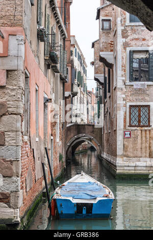VENICE, ITALY - APRIL 1, 2016: A lonely blue boat at an old red house on a canal intersection in Venice. - Stock Photo