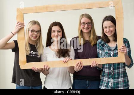 Smiling Girl Quartet With Photo Frames - Stock Photo