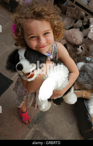 A smiling girl holding a toy dog - Stock Photo