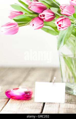 Pink Flowers In A Vase Next To A Lamp With Ornate Metallic Base And