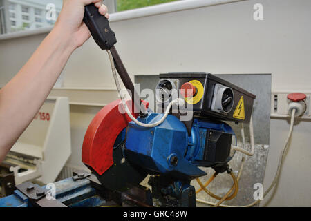 Person Cuts Metal With Chop Saw - Stock Photo